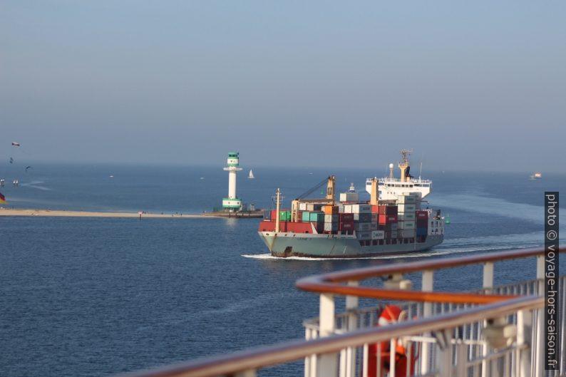 Un petit porte-containeurs passe entre le phare de Friedrichsort et le ferry Color Magic. Photo © André M. Winter