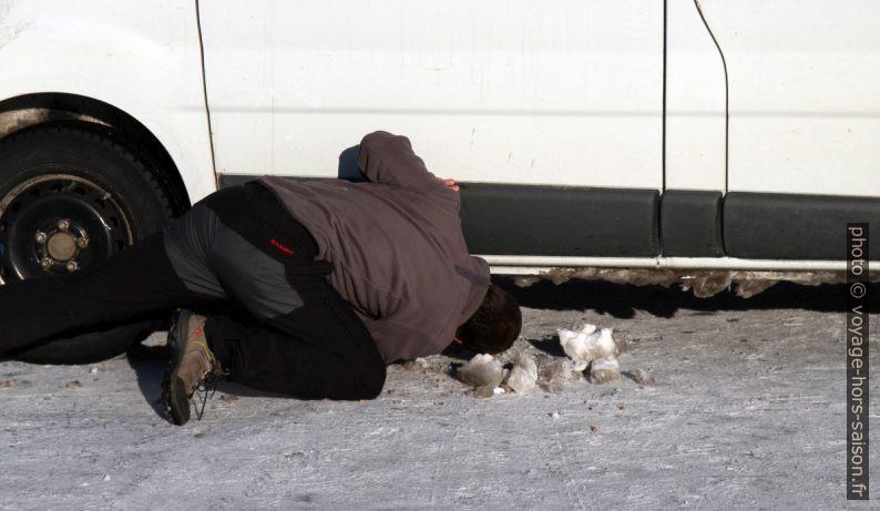 André enlève la glace sous la voiture. Photo © Alex Medwedeff