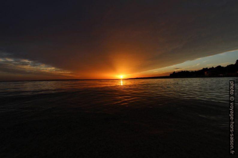 Le soleil passe sous le gros nuage avant de se coucher. Photo © André M. Winter