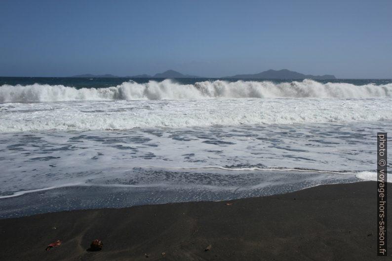 Les Saintes derrière une grande vague sur la Grande Anse. Photo © Alex Medwedeff