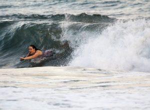 Une femme nage avec une déferlante. Photo © André M. Winter