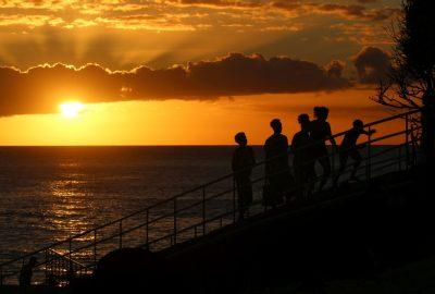 Des jeunes sur l'escalier menant au Phare de Vieux-Fort lors du coucher du soleil. Photo © André M. Winter