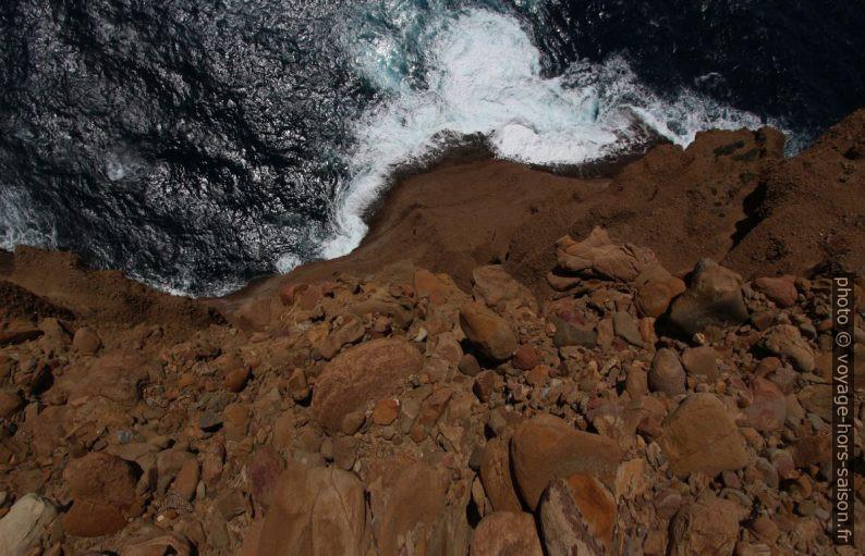 Vue verticale par-dessus la paroi de poudingue vers la mer. Photo © André M. Winter