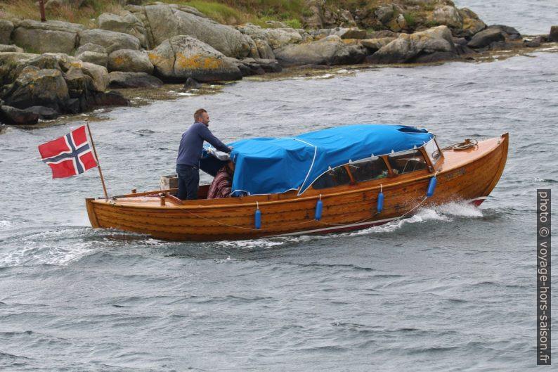 Un bateau en bois rentre dans l'anse de Loshavn. Photo © André M. Winter