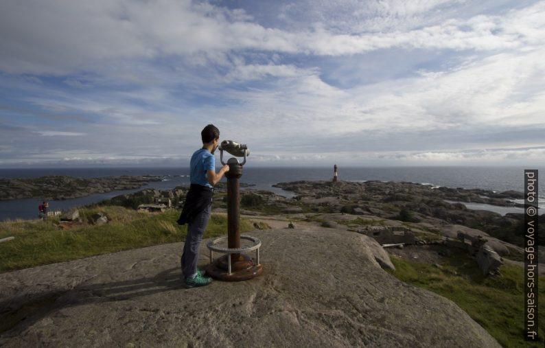 Nicolas vise le Phare d'Eigerøy avec une longue-vue. Photo © André M. Winter