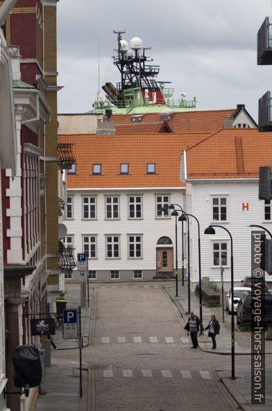 Le mât radar d'un navire de haute mer dépasse des maisons. Photo © André M. Winter