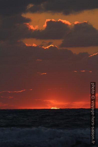 Dernier morceau du disque du soleil au-dessus de la mer. Photo © André M. Winter
