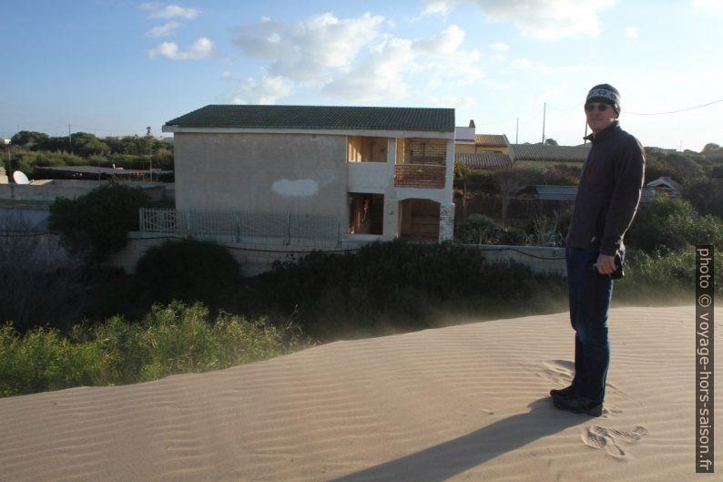 André sur une dune qui menace les maisons. Photo © Alex Medwedeff