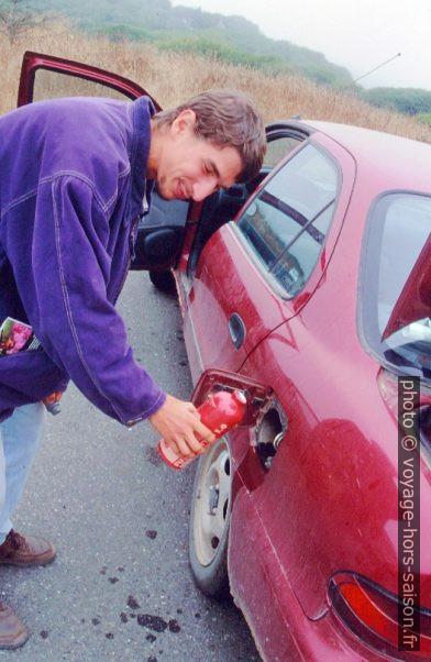 Christian verse de l'essence du réchaud dans le réservoir de la voiture.. Photo © André M. Winter
