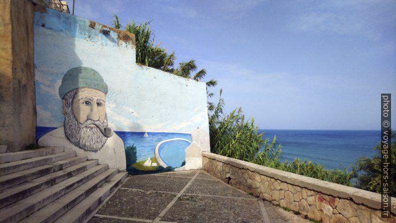 Escalier avec un mur peint d'une tête de marin à Rodi Garganico. Photo © André M. Winter