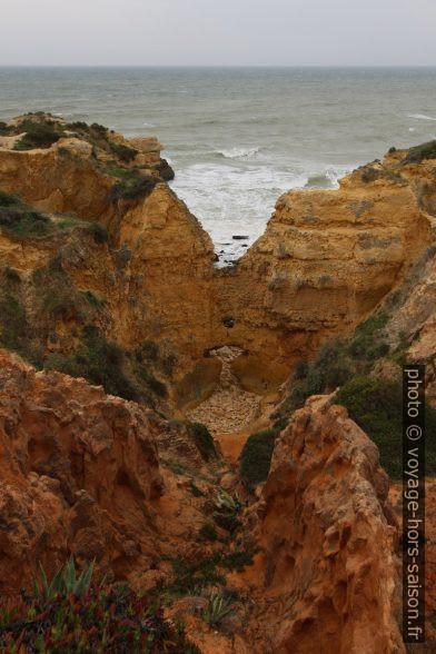 Mur de falaise percé à la base. Photo © André M. Winter