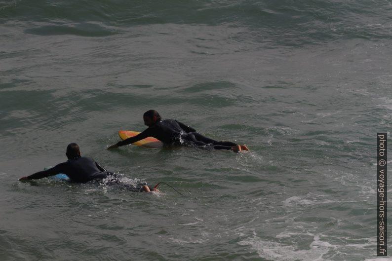 Deux surfeur sur leur planches en train de sortir vers les vagues. Photo © André M. Winter