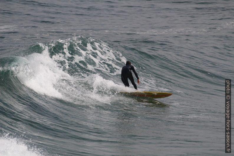 Un surfeur descend sur un court versant de vague. Photo © André M. Winter