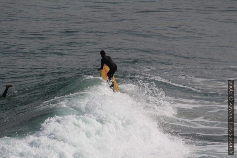 Un surfeur à planche jaune au dernier bout de sa vague. Photo © André M. Winter