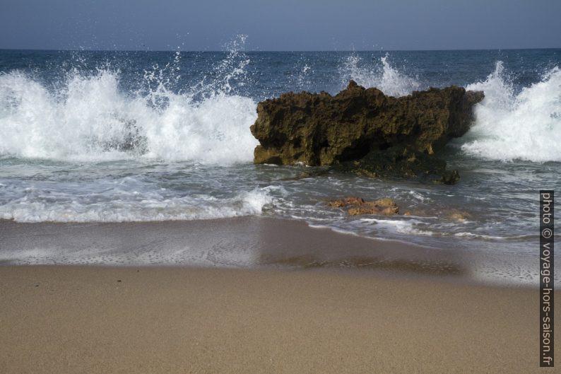 Vague qui éclate derrière un rocher sur la plage. Photo © André M. Winter