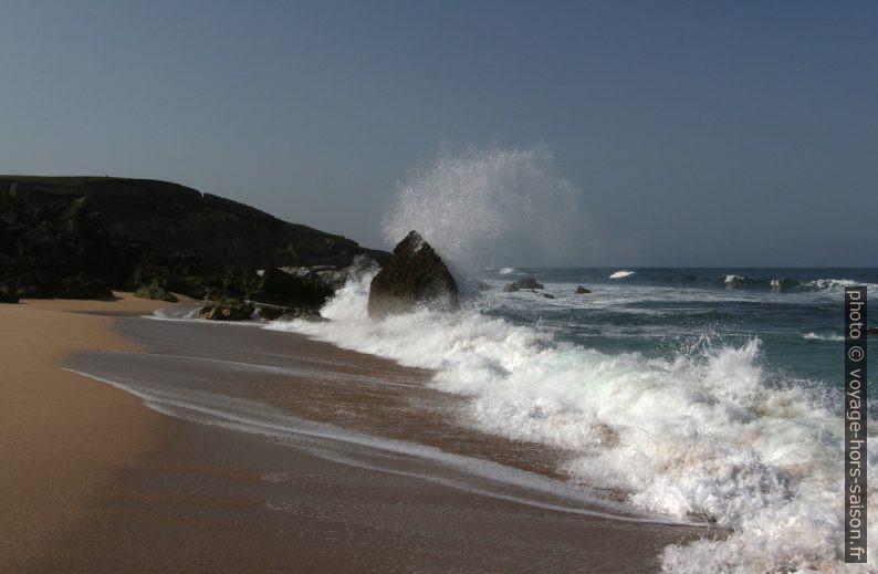 Une vague arrive sur la plage et éclate contre un rocher. Photo © André M. Winter