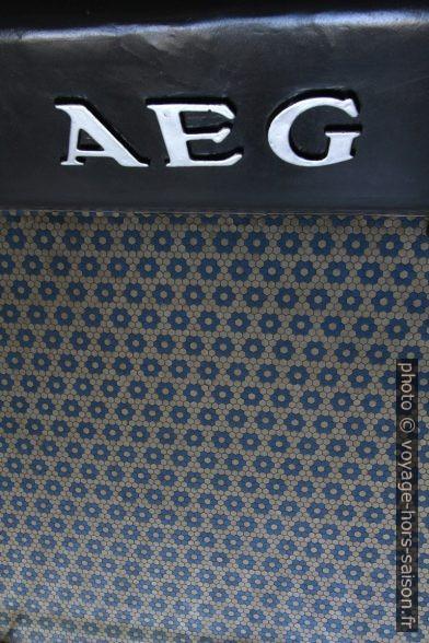 Logo de AEG et carrelage du sol bleu et blanc hexagonal. Photo © André M. Winter