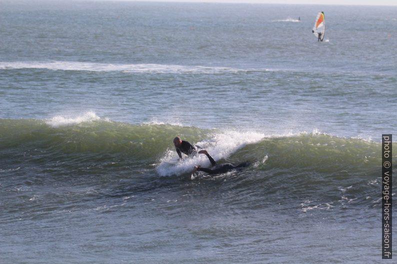 Un surfeur se lance pendant qu'un autre plonge. Photo © André M. Winter