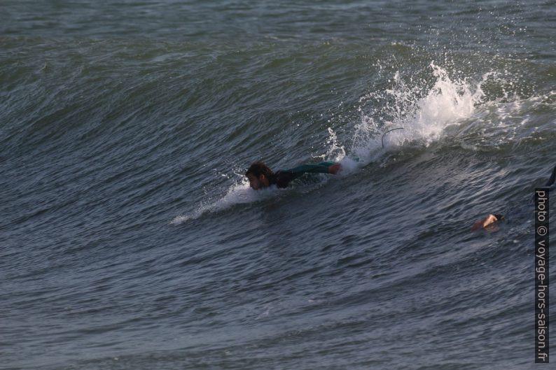 Un surfeur prend de l'élan en ramant. Photo © André M. Winter