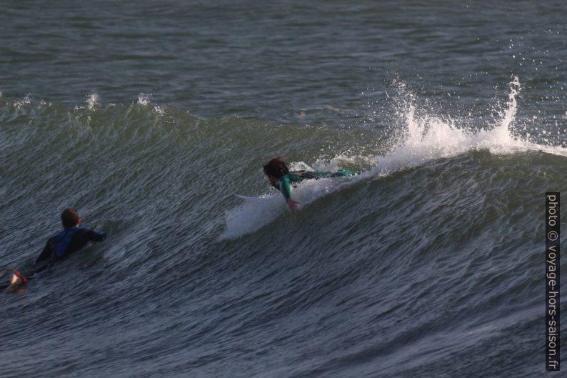 Un surfeur prend de l'élan sur une vague. Photo © André M. Winter