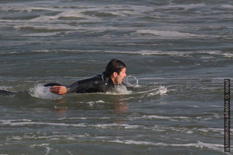 Surfeur ramant pour sortir vers les vagues. Photo © André M. Winter