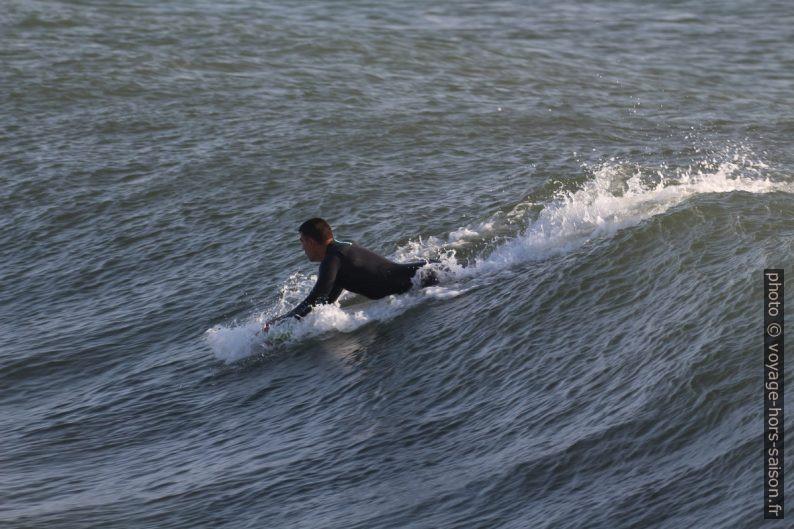 Un surfeur prend de l'élan sur la vague. Photo © André M. Winter