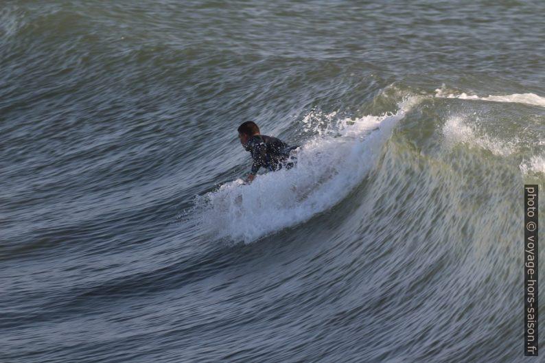 Un surfeur s'élance sur la vague. Photo © André M. Winter