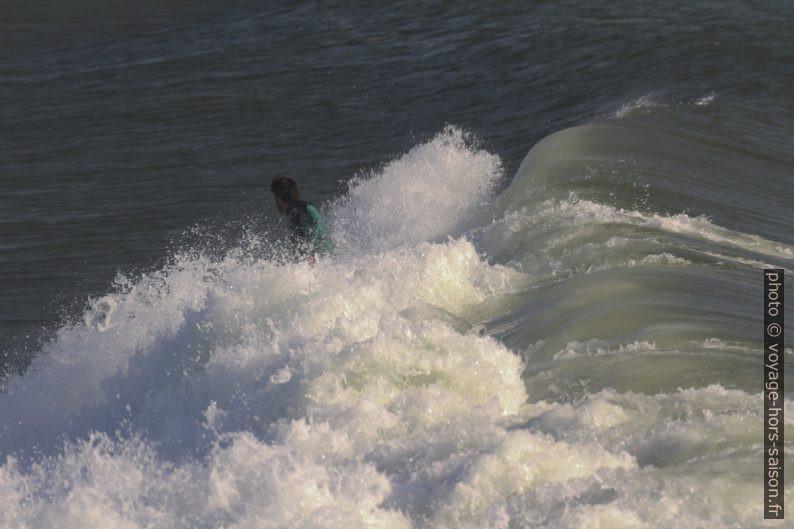 Un surfeur pris dans la mousse de la déferlante qui se brise. Photo © André M. Winter