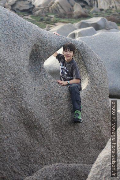 Nicolas assis dans un trou dans la roche. Photo © André M. Winter