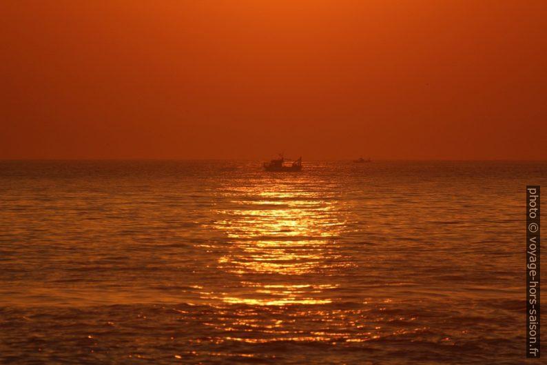 Des bateaux de pêche dans le coucher de soleil orange. Photo © André M. Winter