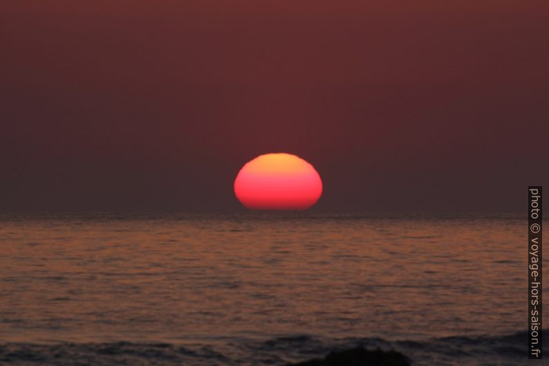 Le disque du soleil plonge d'un tiers dans la mer. Photo © André M. Winter