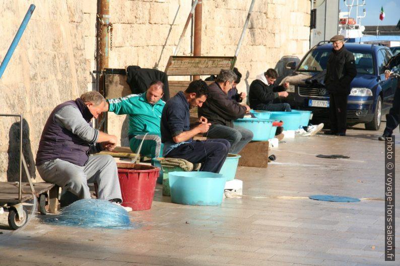 Pêcheurs travaillant à leurs lignes sur le port de Monopoli. Photo © Alex Medwedeff