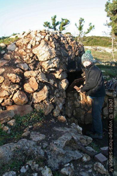 Nicolas devant un fumoir en pierre et en terre. Photo © André M. Winter