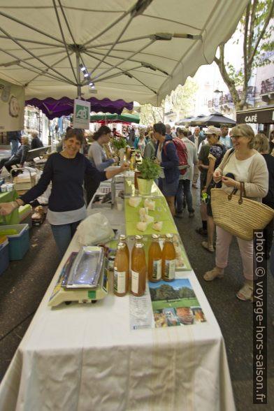 Vendeuse de fromage et de jus bio au marché de Digne. Photo © André M. Winter